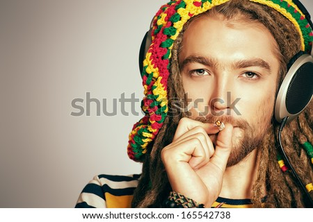 Portrait of a happy rastafarian young man listening to music in headphones. - stock photo