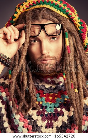 Portrait of a happy rastafarian young man smiling at camera. - stock photo