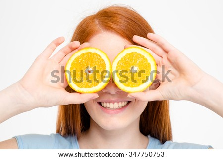 Portrait of a happy redhead woman covering eyes with orange isolated on a white background
