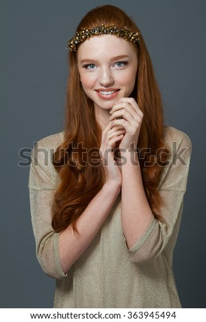Portrait of a happy redhead woman posing over gray bakground - stock photo