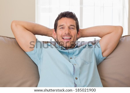 Portrait of a happy relaxed young man sitting on couch at home