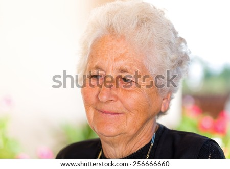 Portrait of a happy retired elderly woman  - stock photo
