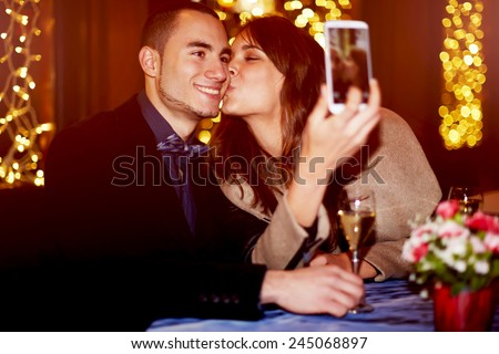 Portrait of a happy romantic couple making selfie photo with smart phone, cheerful girlfriend kissing her boyfriend on the cheek while taking self portrait