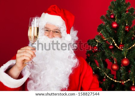 Portrait of a happy santa holding wine glass over red background