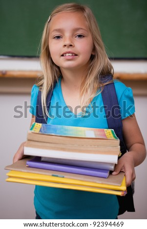 Portrait of a happy schoolgirl holding her books in a classroom - stock photo