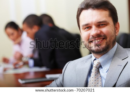 Portrait of a happy senior business man at office with his business team working behind