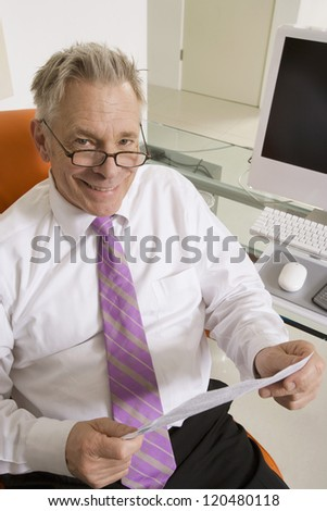 Portrait of a happy senior businessman holding document at office