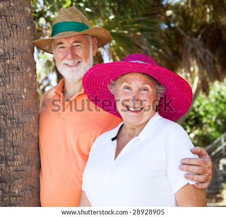 Portrait of a happy senior couple on vacation wearing their sun hats. - stock photo
