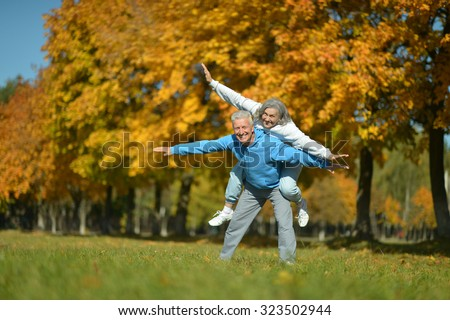Portrait of a happy senior couple resting at autumn park - stock photo