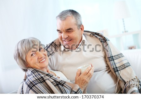 Portrait of a happy senior couple wrapped in plaid sitting at home  - stock photo