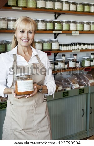 Portrait of a happy senior female employee holding spice jar in store - stock photo