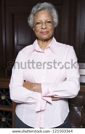 Portrait of a happy senior lawyer standing with hands folded in courtroom
