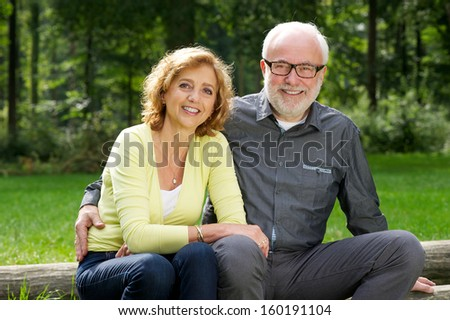 Portrait of a happy senior man and woman sitting together outdoors - stock photo