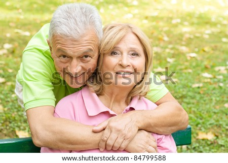 Portrait of a happy senior man embracing her wife in the park. - stock photo
