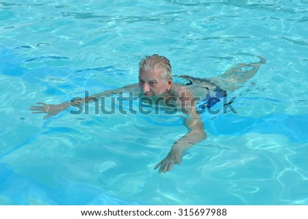 Portrait of a happy senior man in a swimming pool - stock photo