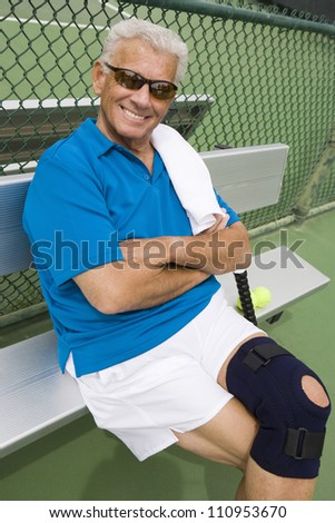 Portrait of a happy senior man relaxing on bench after playing tennis - stock photo