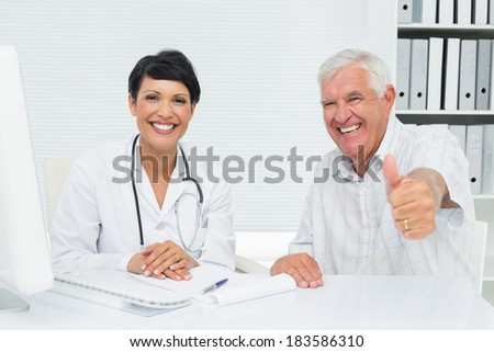 Portrait of a happy senior patient gesturing thumbs up with doctor at the medical office - stock photo