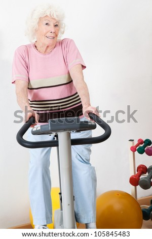 Portrait of a happy senior woman exercising on bike in gym