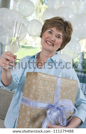 Portrait of a happy senior woman holding gift and champagne flute at party - stock photo