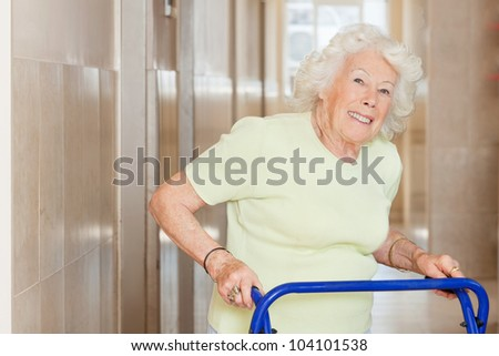 Portrait of a happy senior woman in hospital using Zimmer frame - stock photo