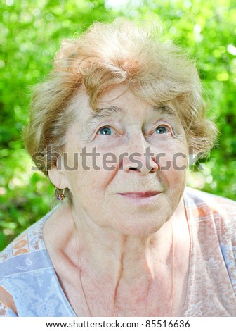 portrait of a happy senior woman in the garden - stock photo