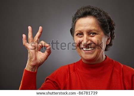 Portrait of a happy senior woman making ok sign - stock photo