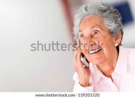 Portrait of a happy senior woman on the phone - stock photo