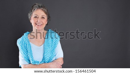 Portrait of a happy senior woman over grey background. - stock photo