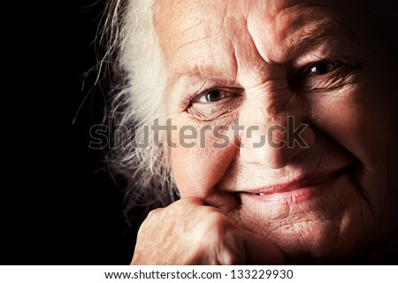 Portrait of a happy senior woman smiling at the camera. Over black background. - stock photo