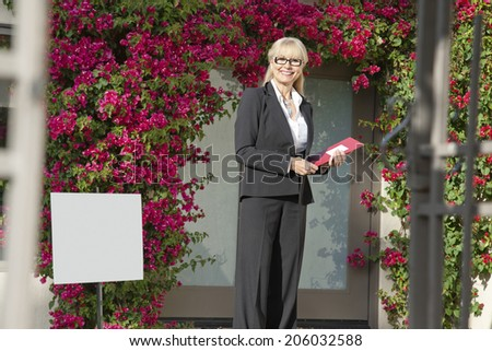 Portrait of a happy senior woman standing with clipboard