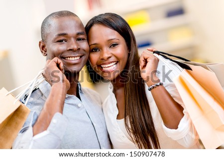 Portrait of a happy shopping couple holding bags - stock photo
