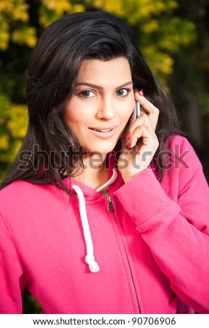 portrait of a happy smiling beautiful girl talking on her mobile phone - stock photo