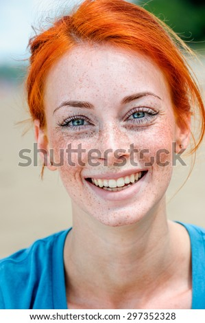 Portrait of a happy smiling beautiful young redhead woman with blue eyes and freckles  - stock photo