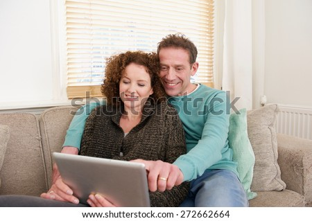 Portrait of a happy smiling couple using computer tablet at home - stock photo