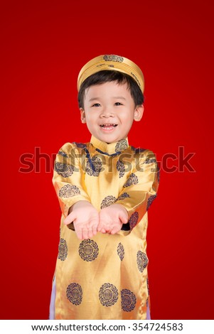 Portrait of a happy smiling handsome Asian baby boy on traditional festival costume. Cute little Vietnamese boy in ao dai dress smiling.
