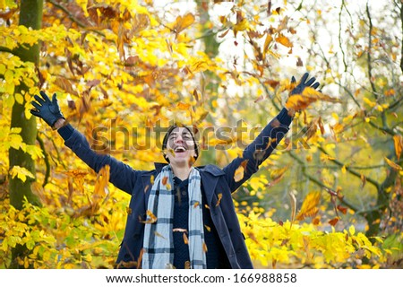 Portrait of a happy smiling man throwing leaves with open arms in autumn - stock photo