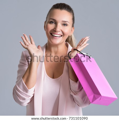 Portrait of a  happy smiling surprise woman with pink  shopping bag. Attractive cheerful female holds the  bag with purchasing.