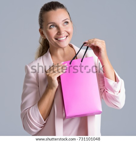 Portrait of a  happy smiling woman with pink  shopping bag. Attractive cheerful female holds the  bag with purchasing.