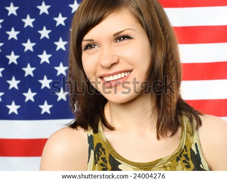 portrait of a happy smiling young woman standing near the American flag