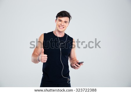 Portrait of a happy sports man holding smartphone with headphones and showing thumb up isolated on a white background - stock photo