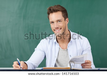 Portrait of a happy student in front of a green chalkboard