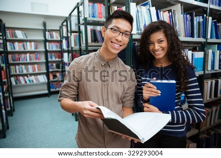 Portrait of a happy students searching books in library - stock photo