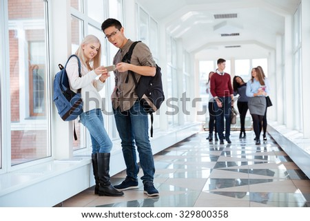 Portrait of a happy students using smartphone in the university hall - stock photo