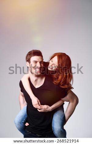 Portrait of a Happy Sweethearts - Young Handsome Man Carrying his Girlfriend on his Back at the Studio with Gray Background. - stock photo