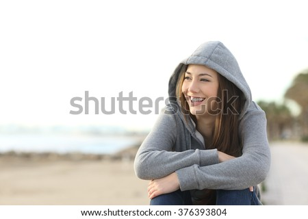 Portrait of a happy teenager girl smiling and looking at side outside on the beach - stock photo