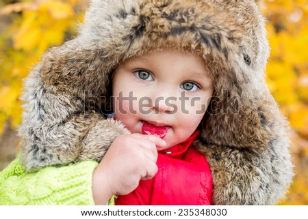 Portrait of a happy toddler child eating candy - stock photo