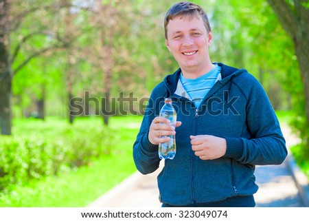 portrait of a happy trainer with a bottle of water during a break between workouts - stock photo