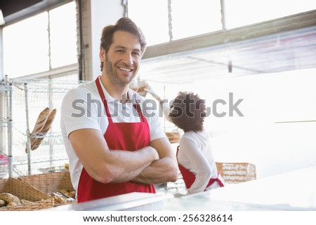 Portrait of a happy waiter with arms crossed at the bakery - stock photo
