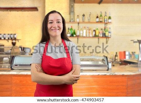 portrait of a happy waitress with crossed arms standing at the bar