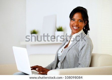 Portrait of a happy woman browse the Internet on laptop while is sitting on sofa at home